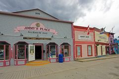 DAWSON STAD, YUKON, KANADA, JUNI 24 2014: Historiska byggnader och typiska traditionella trähus i en huvudsaklig gata in Fotografering för Bildbyråer