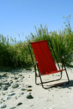 Day at the beach. Red chair standing in the sand with high grass around it Royalty Free Stock Photography