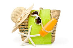 Day At The Beach. Beach bag with items for a day at the seaside on white background Royalty Free Stock Image
