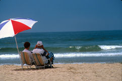 Day at the beach. Couple enjoying the beach in their chairs and unbrella by the waves royalty free stock photography