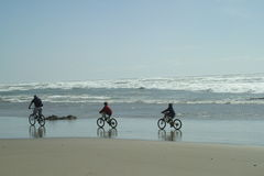 Day at the beach. Bicycling on the surf Royalty Free Stock Image