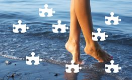 Day at the beach puzzle. Puzzle picture of female legs in blue water Royalty Free Stock Photography