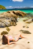 Day at the beach. Young woman with curly hair sunbathing on an exotic island Stock Photo