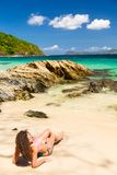 Day at the beach. Young woman with curly hair sunbathing on an exotic island Royalty Free Stock Photo