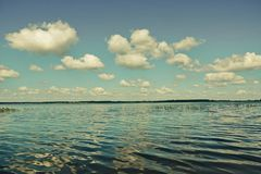 Day beautiful white clouds over the lake reflected clouds waves. Any Royalty Free Stock Images