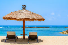 Day bed lounger under the shade of a thatched roof hut Stock Photo