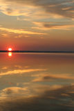 The day begins. The sun both sea and cloud. Early morning. The sun rises above the sea and gold clouds. In the quiet sea beautiful reflection. Pleasant colours royalty free stock image