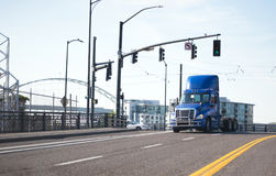 Day cab blue semi truck tractor going by urban city street Stock Image