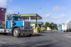 Day cab vintage big rig blue semi truck with semi trailer moving on truck stop with fuel station. Shiny blue classic American bonnet day cab big rig semi truck royalty free stock photos