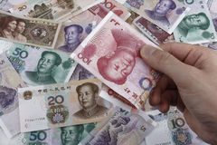 A Day In China (Chinese money RMB). Holding a Chinese 100 RMB banknote in the right side of the picture. Chinese bills in the background Stock Photos