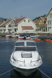 Day-cruiser and water-front houses. Fast day-cruiser and water-front houses in Farsund, a small town on the south coast of Norway Stock Image