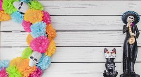Day of the Dead background - White painted plank background with colorful skull wreath on one side and Mexican skeleton mariachi p. Layer and dog with colorfully stock photos