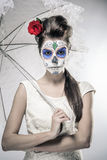 Day of the dead girl. With sugar skull makeup holding lace umbrella Stock Images