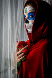 Day of the dead girl. With sugar skull makeup holding red rose Royalty Free Stock Image