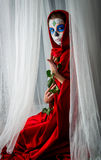Day of the dead girl. With sugar skull makeup holding red rose Royalty Free Stock Photo