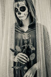 Day of the dead girl. With sugar skull makeup holding rose, black and white photo Royalty Free Stock Photography