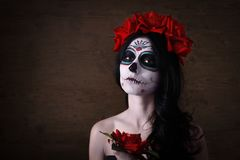 Day of the dead. Halloween. Young woman in day of the dead mask skull face art and rose. Dark background. Young woman in day of the dead mask skull face art and stock photos