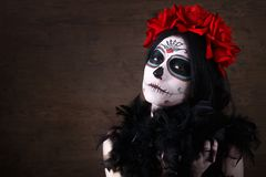 Day of the dead. Halloween. Young woman in day of the dead mask skull face art and rose. Dark background. stock photo