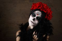 Day of the dead. Halloween. Young woman in day of the dead mask skull face art and rose. Dark background. royalty free stock photo