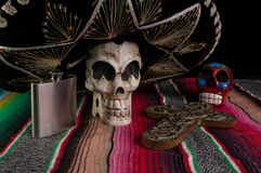 Day of The Dead Skull. Day of The Dead (Dia de los Muertos) skull with with decorative cross, tequila flask on a traditional mexican blanket royalty free stock image