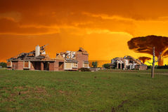 Doomsday Destruction. Mushroom clouds rise behind a destroyed neighborhood in this artistic depiction of a future doomsday. Smoke billows against a firey orange Royalty Free Stock Photography