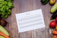 7 day diet plan on table full of fruits and vegetables. On wooden table Stock Photos