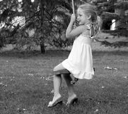 Day dream believer. A little girl silently sitting on a swing lost in her own thoughts and or world Stock Photos