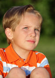 Day Dreamer. Little boy outdoors with a serious look on his face Royalty Free Stock Image