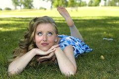 Day dreaming. Young woman day dreaming in the park Stock Image
