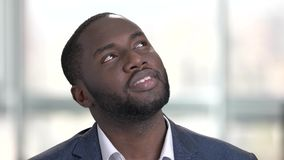 Day dreaming black businessman face in bright office. stock video
