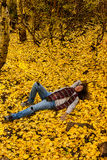 Day Dreaming in Fall Leaves. Woman day dreams on a bed of fall aspen leaves royalty free stock photo