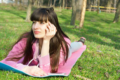 Day dreaming. Happy brunette woman lying on the grass on a mat and enjoying the bright sunny day, dreaming about something royalty free stock image