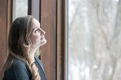 Young woman day dreaming and looking out window. A day dreaming hopeful young woman smiling and looking up above out a window in winter royalty free stock photography