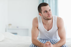 Day dreaming man sitting on his bed Stock Image