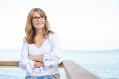 Day dreaming at the sea. Portrait of a happy attractive middle aged woman looking away day dreaming royalty free stock photo