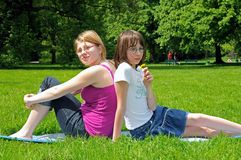 Day-dreaming sisters. Two day-dreaming girls sitting in the grass Stock Image