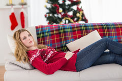 Day dreaming young woman lying on couch Stock Photography