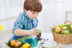 The day before Easter, beautiful child painting eggs for easter Stock Images