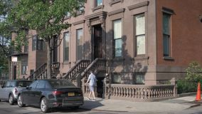 Day Establishing Shot of Typical Brooklyn Brownstone Home. A daytime exterior establishing shot of a typical Brooklyn brownstone residential home stock video footage