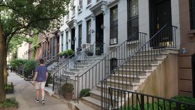 Day Establishing Shot of Typical Row Houses in Manhattan. A daytime establishing shot DX of typical upscale row houses or brownstones lining a residential street stock footage