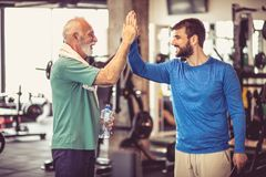 Day of at gym. Personal trainer talking and with senior men at gym stock photo