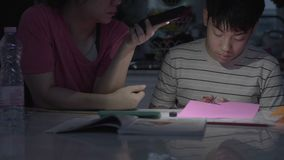 Asian mothers Helping my son do art using the phone light To finish the job. stock footage