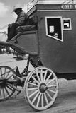 Day job. Tired old cowboy driving stagecoach royalty free stock image