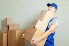 Day moving. Delivery of goods from shopping in the online store. Loader or courier transports cardboard boxes against gray wall stock photo