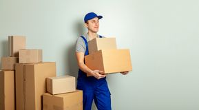 Day moving. Delivery of goods from shopping in the online store. Loader or courier transports cardboard boxes against gray wall royalty free stock images