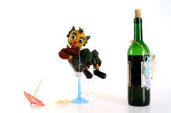 The day after the night before. A puppet in a wine glass, with wine bottle, paper umbrella and paper streamers royalty free stock images