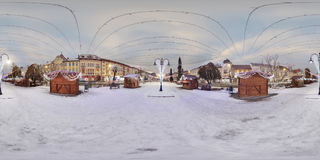 Day-night composite of Targu Mures Town Center in winter. Day-night composite 360 panorama of decorated wooden booths in a snow-covered Piata Trandafirilor Roses Royalty Free Stock Images