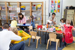 A Day in a Nursery. Class of nursery children doing arts and crafts with their teachers. They are using recycled boxes and cartons stock image