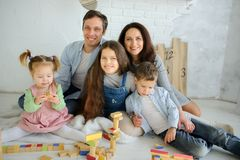Day off in a big family. Dad, mom and three children are sitting on the floor. Younger children are built from tower cubes. Parents and the eldest daughter royalty free stock images