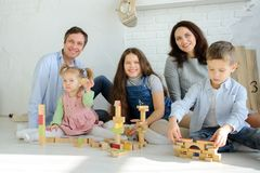 Day off in a big family. Dad, mom and three children are sitting on the floor. Younger children are built from tower cubes. Parents and the eldest daughter royalty free stock photography